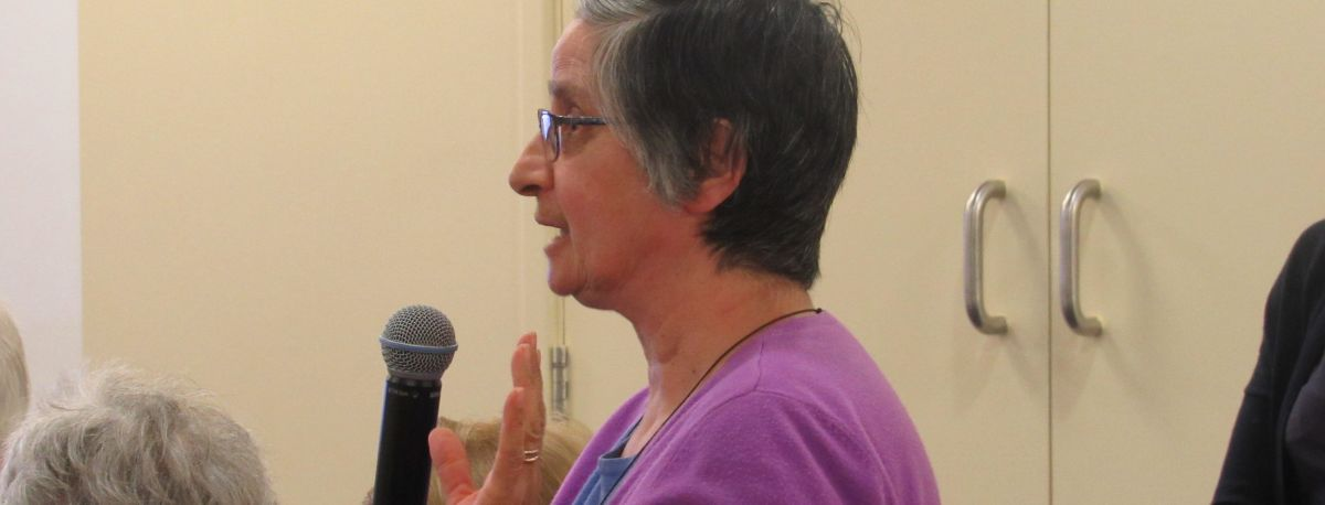 carer at meeting speaking about funding cuts
