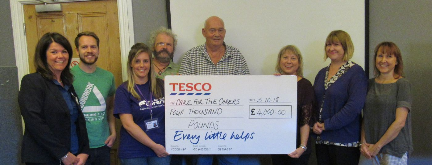 photo of carers holding large cheque dontation from Tesco